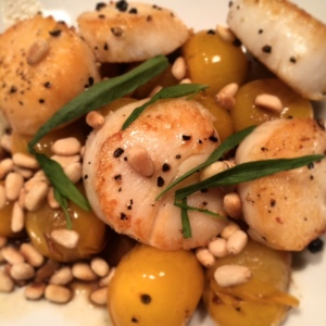 Scallops with pine nuts (works fine in place of hazelnuts), and sun gold tomatoes.